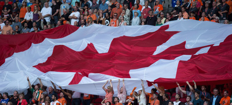 Fans hold up a large Canadian flag during the singing of the national anthem before the B.C. Lions and Saskatchewan Roughriders play a CFL football game in Vancouver, B.C., on Friday July 10, 2015. THE CANADIAN PRESS/Darryl Dyck